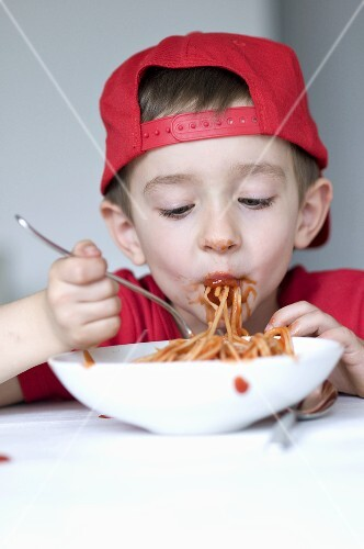 little boy eating spagetti