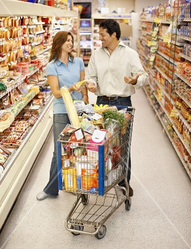 Man and Woman Grocery Shopping; Full Grocery Cart